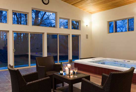 Nicely lit indoor space large windows with a swim spa