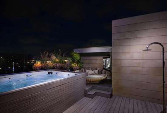 Nighttime view of swim spa on patio with shower