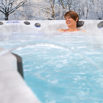 Woman relaxing in swim spa in the cold winter weather