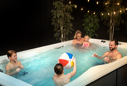 Family enjoying and playing with a beach ball in their swim spa