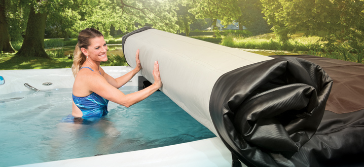 woman rolling up the axis cover system while inside her swim spa
