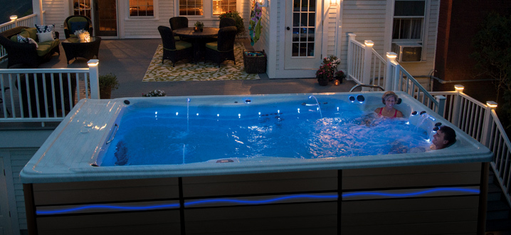 a swim spa lit at night with the wave lighting on the side